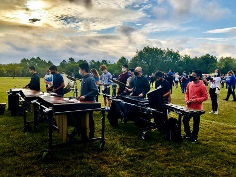 George Vera, band director at Elmwood Middle School, performs with the rest of the front ensemble on their halftime show.